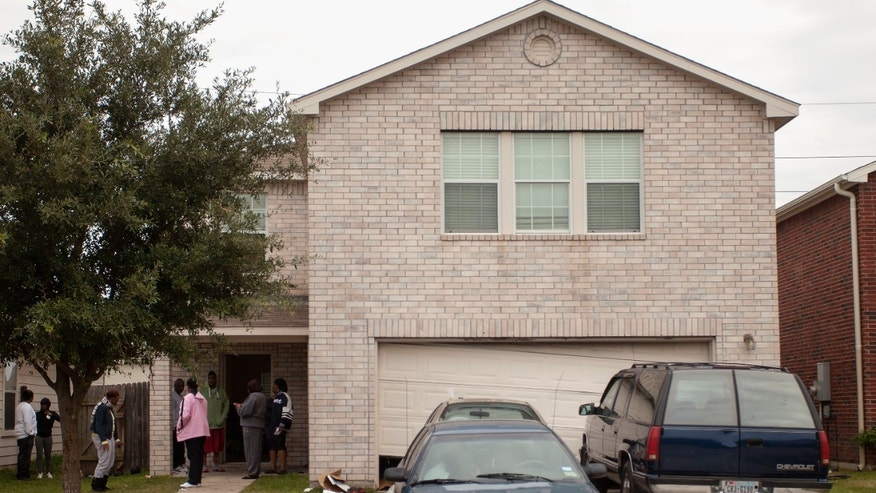 FILE - In this Nov. 10, 2013 file photo, people gather at  a home in Cypress, Texas, the morning after two people were killed and 19 were injured when gunfire rang out at a house party there.Willie Young, 21, and Randy Stewart, 18, were arrested in connection with the shooting Monday, Nov. 1, 2013 according to the Harris County Sheriff's Office. Young is charged with deadly conduct while Stewart is charged with aggravated assault. (AP Photo/Bob Levey, File)