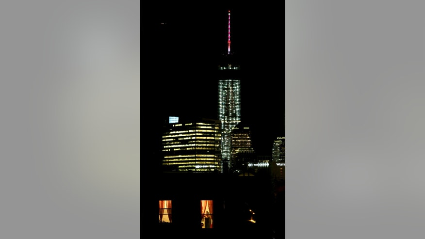 A woman talking on a phone is seen through a window of a home in The Heights neighborhood of Jersey City, N.J., with One World Trade Center as a backdrop, Friday, Nov. 8, 2013. The Port Authority of New York and New Jersey, who tested the lights on Friday, said the beacon is packed with nearly 300 modules and their glow can be seen for up to 50 miles. The beacon and spire together stand 408 feet tall and bring the building, formerly called the Freedom Tower, to its symbolic height of 1,776 feet. The Durst Organization operates the spire, which will serve broadcasters. (AP Photo/Julio Cortez)