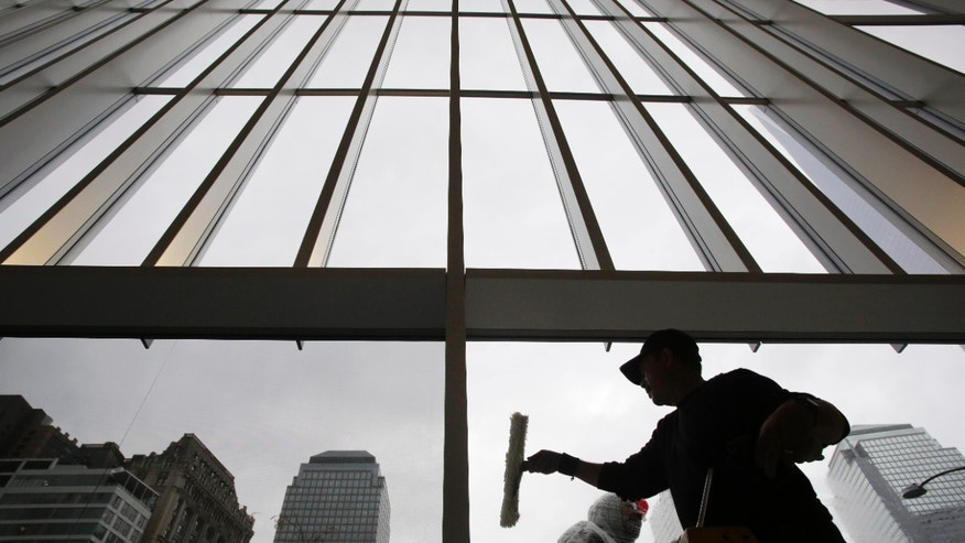 Workers clean the glass windows at the lobby of 4 World Trade Center, Thursday, Nov. 7, 2013, in New York.  The 1,776-foot One World Trade Center is the marquee skyscraper at ground zero&#x3b; but the first office tower to open there will be its shorter neighbor 4 World Trade Center on Wednesday, Nov. 13. (AP Photo/Mark Lennihan)