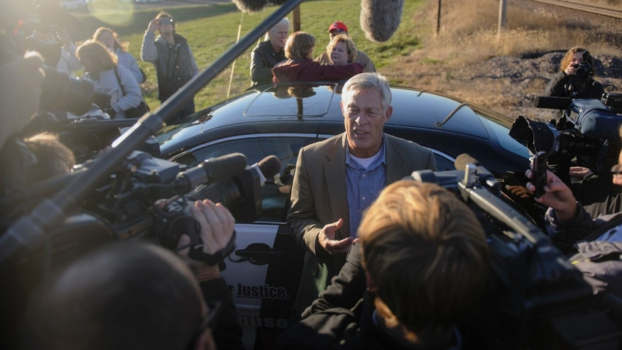 Bill Ferguson, center, speaks with members of the media about his his son's pending release from prison on Tuesday, Nov. 12, 2013 near the Jefferson City Correctional Center in Jefferrson City, Mo.  The Missouri attorney general said Tuesday that he won't seek to retry a man whose 2005 murder conviction and 40-year prison sentence in the slaying of a newspaper sports editor were recently overturned. (AP Photo/Columbia Daily Tribune, Nick Schnelle)