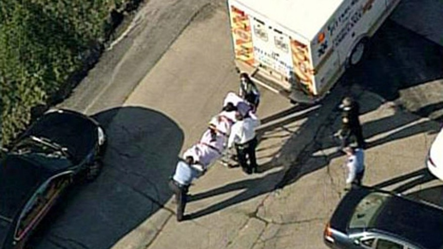 In this aerial image provided by KDKA-TV, a person is loaded into an ambulance near Brashear High School in Pittsburgh, Wednesday, Nov. 13, 2013. Pittsburgh police reported Wednesday that three people were shot near the school. The condition of the person in the stretcher was unknown Wednesday. (AP Photo/KDKA-TV)