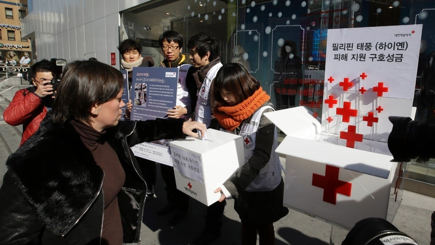 "FILE - In this Wednesday, Nov. 13, 2013 file photo, a tourist donates money for the victims of Typhoon Haiyan in the Philippines during a fund-raising campaign on a street in Seoul, South Korea. Signs read, ""Aid donation for the victims of Typhoon Haiyan."" (AP Photo/Lee Jin-man)"