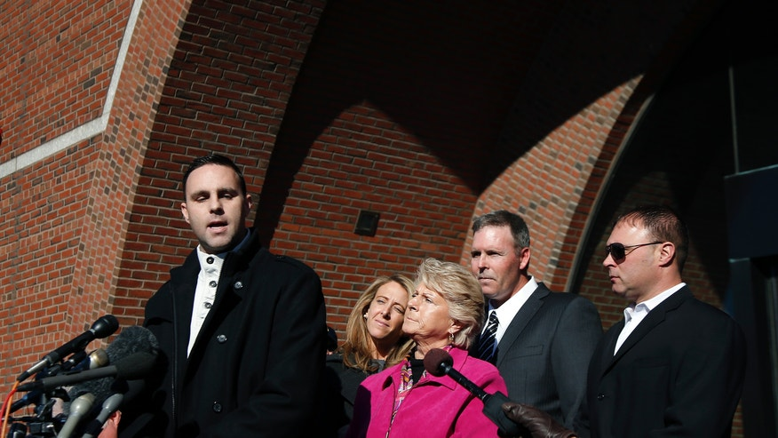 "Tommy Donahue, son of Michael Donahue, speaks to the media as his fiancee Michelle Carter, his mother Patricia Donahue, and his brothers Shawn and Michael Jr. (far right) listen outside federal court in Boston, Thursday, Nov. 14, 2013. Former Boston crime boss James ""Whitey"" Bulger was sentenced Thursday to life in prison for his murderous reign in the 1970s and '80s, bringing to a close a case that exposed FBI corruption so deep that many people across the city thought he would never be brought to justice. Bulger was found guilty in Michael Donahue's 1982 murder. (AP Photo/Elise Amendola)"