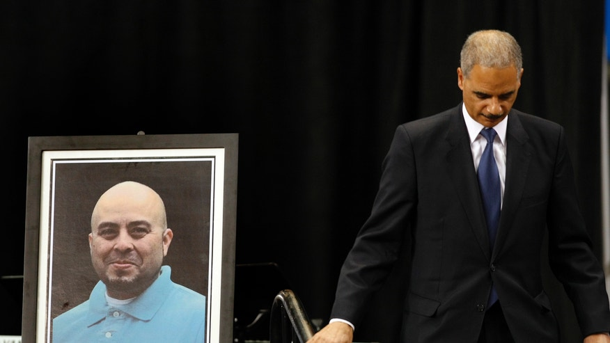 Nov. 12, 2013: Attorney General Eric Holder walks past a portrait of slain TSA officer Gerardo Hernandez after delivering remarks during the public memorial service for Hernandez. Hernandez was the first TSA officer killed in the line of duty when a gunman pulled a rifle from a bag and shot the 39-year-old father of two on Nov. 1 at Los Angeles International Airport. Two TSA officers and a teacher were injured before airport police wounded the gunman, Paul Ciancia.  (AP/ Los Angeles Times, Al Seib, Pool)