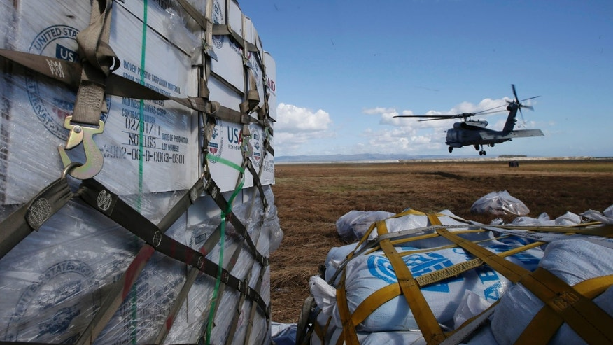 A U.S. Navy Sea Hawk helicopter from the U.S. aircraft carrier USS George Washington takes off to air drops relief supplies to villages isolated by last week's typhoon at Tacloban City airport, Leyte province in central Philippines, Friday Nov.15, 2013. The Philippines has received an outpouring of international aid running into hundreds of millions of dollars but much of it has been stuck in a bottleneck outside the affected areas. (AP Photo/Bullit Marquez)