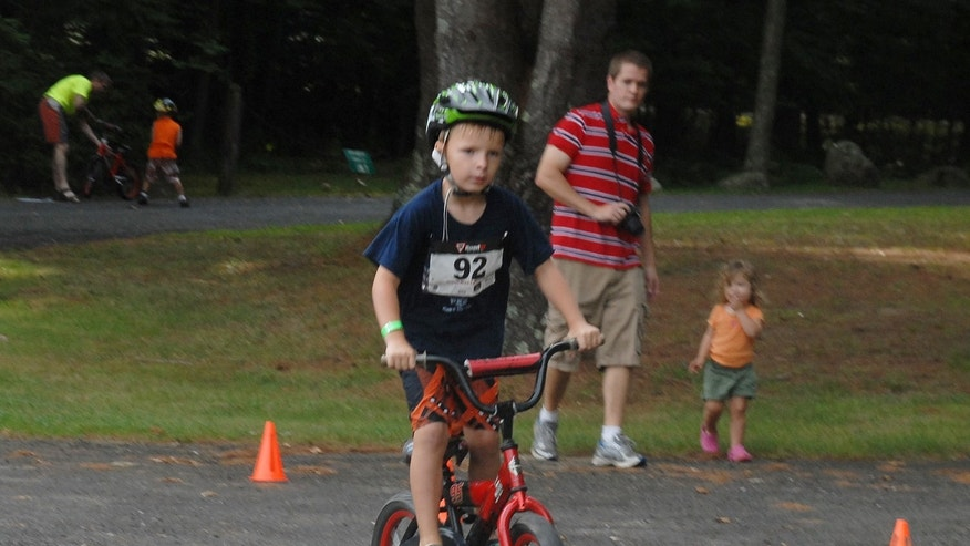 In this 2012 file photo provided by the Kowalski family, Chase Kowalski bikes during the 2012 Kids Who Tri Succeed Triathlon in Mansfield, Conn. Chase Kowalski loved to race, whether it was running, swimming or riding his bike. The 7-year-old, one of 26 people killed last Dec. 14 inside the Sandy Hook Elementary school, ran competitively for the first time when he was just 2½ years old. His parents decided to honor Chase's memory by a starting a foundation, raising money for children's fitness projects, family wellness and preschool education scholarships. (AP Photo/Kowalski family)