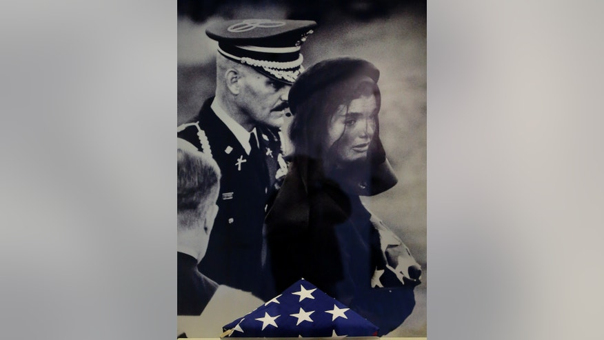 A small new exhibit at the John F. Kennedy Library and Museum marking the 50th anniversary of the assignation of the 35th President of the United States includes never-before-displayed artifacts from his three-day state funeral, such as the American flag which draped the president's casket presented with a photograph of first lady Jacqueline Bouvier Kennedy during her husband's funeral in Boston, Thursday, Nov. 14, 2013. (AP Photo/Stephan Savoia)