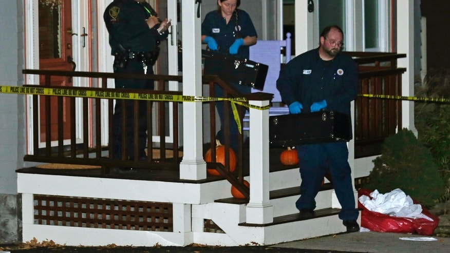 Workers from the Massachusetts medical examiner's office carry two small boxes from a home in a neighborhood of Arlington, Mass., Monday, Nov. 18, 2013. Authorities have identified the four people found dead at the home in the Boston suburb as a 43-year-old husband and wife and their two sons, who would have celebrated their first birthdays next week. (AP Photo/Charles Krupa)