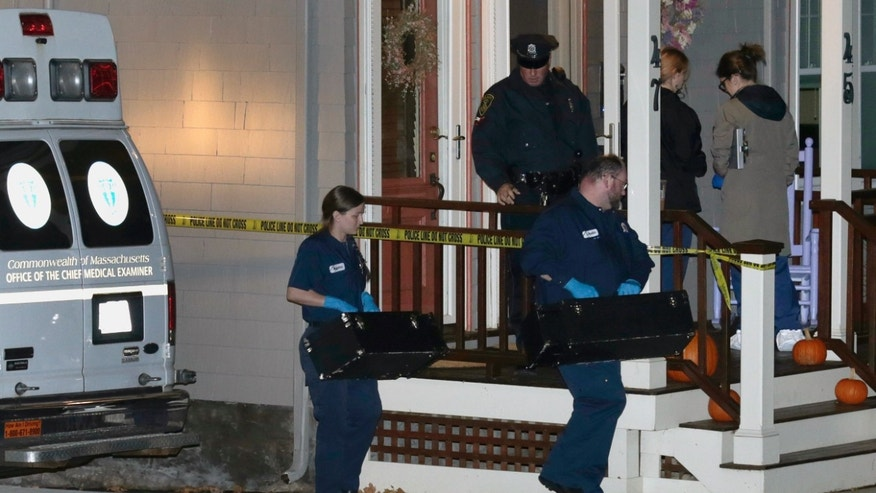 Workers from the Massachusetts medical examiner's office carry two small boxes to a home in a neighborhood of Arlington, Mass., Monday, Nov. 18, 2013. Authorities have identified the four people found dead at the home in the Boston suburb as a 43-year-old husband and wife and their two sons, who would have celebrated their first birthdays next week. (AP Photo/Charles Krupa)