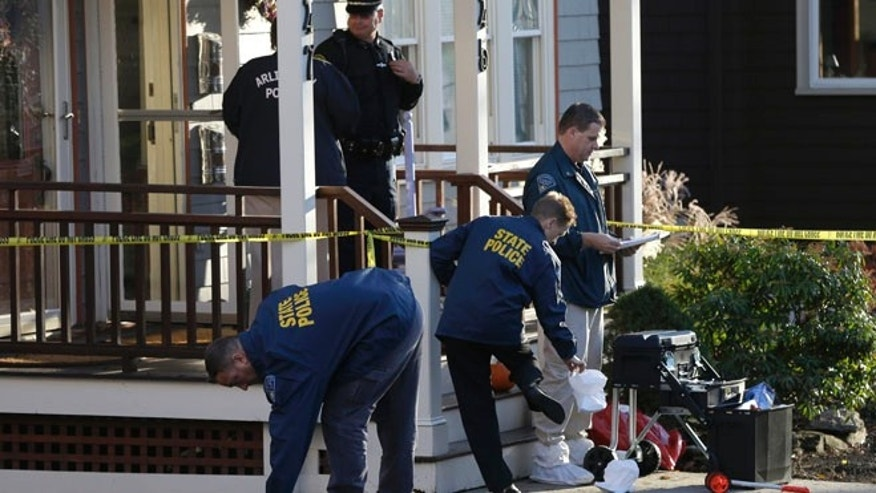 Nov. 18, 2013: Law enforcement officials remove protective slippers outside a two-family home in Arlington, Mass., where four people were found dead.