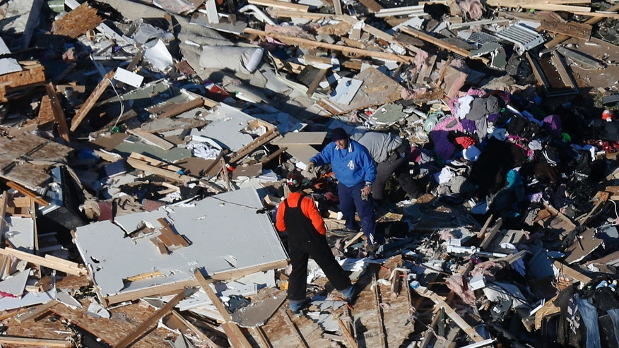 This aerial view on Monday, Nov. 18, 2013, two men walk through what is left of a home that was destroyed by a tornado that hit the western Illinois town of Washington on Sunday. It was one of the worst-hit areas after intense storms and tornadoes swept through Illinois. The National Weather Service says the tornado that hit Washington had a preliminary rating of EF-4, meaning wind speeds of 170 mph to 190 mph. (AP Photo/Charles Rex Arbogast)