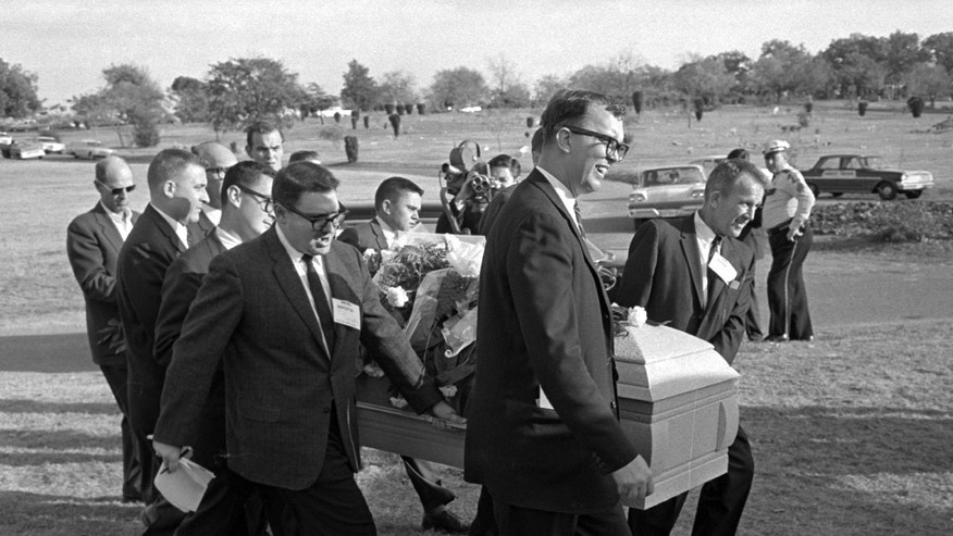 Reporters were enlisted to act as pall bearers at the interment of Lee Harvey Oswald at the Shannon Rose Hill Cemetery. Pallbearers from left end - Jerry Flemmons with crewcut and no glasses. In front of Flemmons are reporters Ed Horn and Mike Cochran. Funeral director Paul J. Groody was among the pallbearers. On the far side of the casket are Jon McConal, rear, and Preston McGraw, front. The pallbearer obscured behind Groody could not be identified. (AP Photo/Gene Gordon)