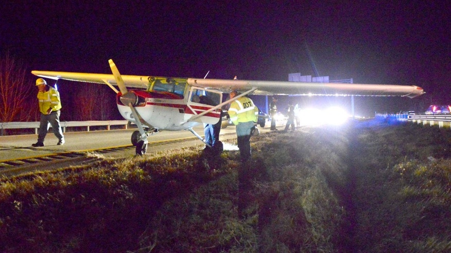 Maine State police and DOT officials look over a small plane that made a emergency landing in the southbound lane of Interstate 295 at mile 13 in Falmouth during evening rush hour traffic on Thursday, Nov. 21, 2013. No injuries were reported. (AP Photo/Portland Press Herald, John Patriquin)