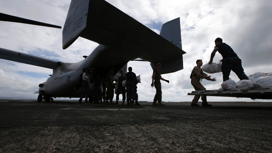 FILE - In this Wednesday, Nov. 20, 2013 file photo, U.S. troops load relief supplies to a U.S. Marine MV-22 Osprey aircraft for airdrop to typhoon-ravaged remote places, at Tacloban airport, Leyte province in central Philippines. The Marines' newest and in some quarters most controversial transport airplane is showing the world what it's got - for the sake of the victims of Typhoon Haiyan, and perhaps its own future. (AP Photo/Bullit Marquez)