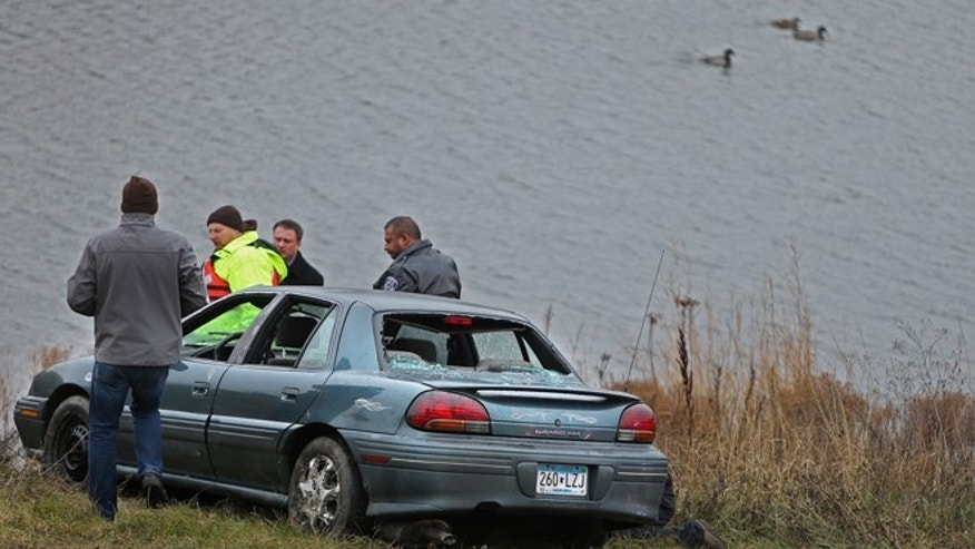 Nov. 21, 2013:  Photo investigators look at a car that veered off a suburban Minneapolis highway ramp and plunged into a storm water pond with five children, ages 1 to 7, aboard.