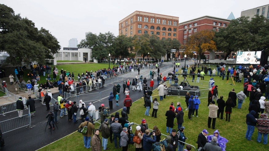 A crowd moves into position before a ceremony to mark the 50th anniversary of the assassination of John F. Kennedy, Friday, Nov. 22, 2013, at Dealey Plaza in Dallas. President Kennedy's motorcade was passing through Dealey Plaza when shots rang out on Nov. 22, 1963. (AP Photo/Tony Gutierrez)