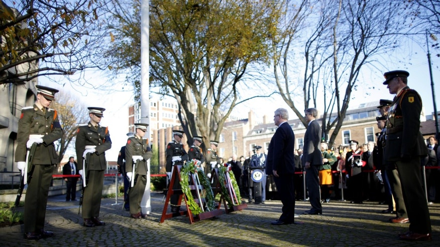 Ireland's Minister for Foreign Affairs and Trade, Eamon Gilmore, centre left, stands during a ceremony to lay a wreath on behalf of the Irish Government, outside the Embassy of the United States of America in Dublin, Ireland, Friday, Nov. 22, 2013. The Irish Defence Forces, as well as the original cadets who served as honour guards at President Kennedy's funeral in 1963, attended the ceremony in Dublin to mark the fiftieth anniversary of the death of US President John F. Kennedy.  (AP Photo/Peter Morrison)