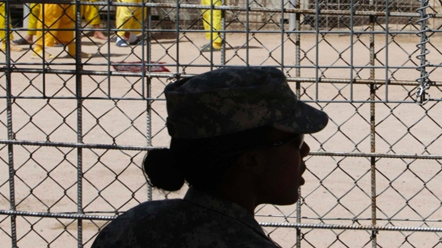 Sept. 16, 2009: A U.S. soldier keeps watch as detainees spend time at Camp Bucca in southern Iraq.