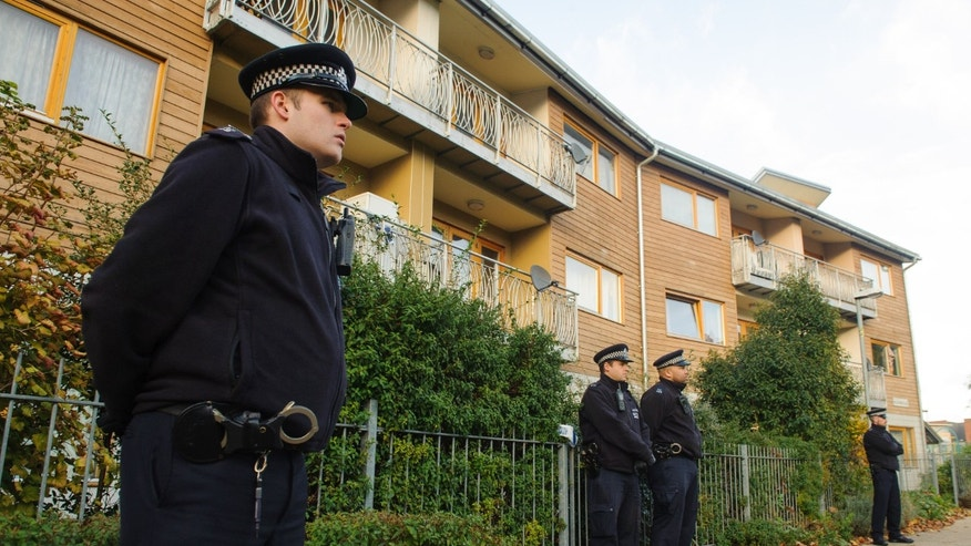 Nov. 23, 2013: Police officers stand outside flats as police conduct house-to-house inquires in the area where three women were rescued in south London.
