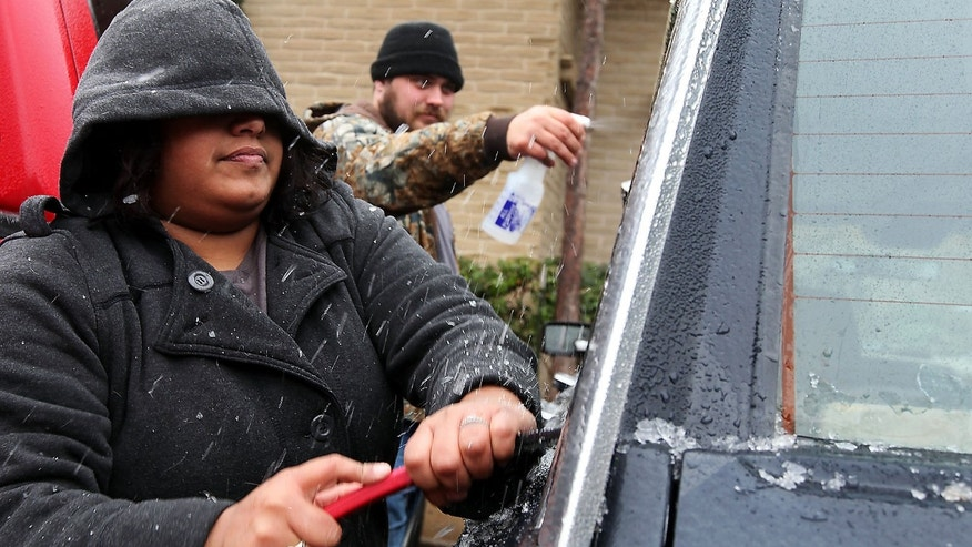 Samantha Hernandez scrapes ice off of the windows after Kenneth Fields sprays them with a concoction of vinegar and water to soften the ice on Saturday, Nov. 23, 2013, in Odessa, Texas. The fierce weather has caused at least eight deaths and prompted advisories Saturday afternoon in New Mexico and Texas. (AP Photo/The Odessa American, Edyta Blaszczyk)