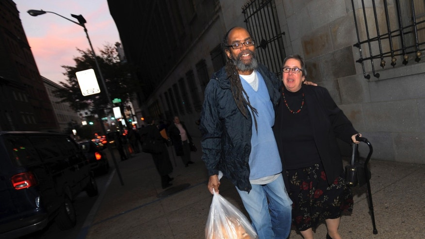 In this photo taken on Thursday, Nov. 14, 2013, freed prisoner Salim Sadiki, who served 37 years after being found guilty of rape, walks away from the courthouse in Baltimore with a friend after being released from prison. Faulty jury instructions given at trials held decades ago have led prosecutors in Maryland to release approximately 50 people, and some 200 prisoners could ultimately be released from Maryland prisons as a result. (AP Photo/Gail Burton)
