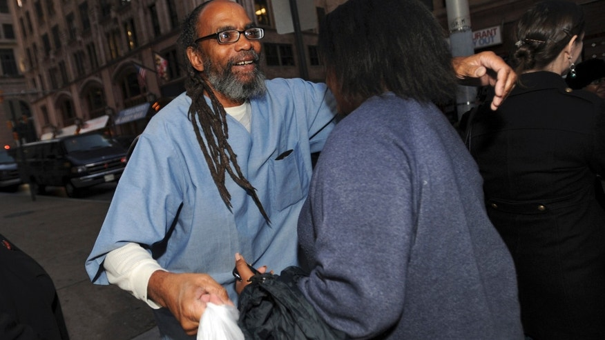 In this photo taken on Thursday, Nov. 14, 2013, freed prisoner Salim Sadiki hugs a family member after walking out of the courthouse in Baltimore, after being released from prison after 37 years. Faulty jury instructions given at trials held decades ago have led prosecutors in Maryland to release approximately 50 people, and some 200 prisoners could ultimately be released from Maryland prisons as a result. (AP Photo/Gail Burton)