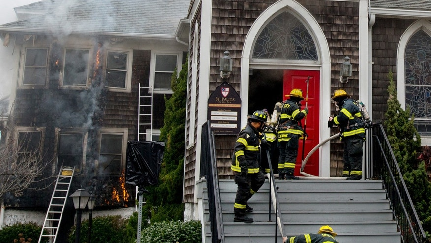 Nov. 26, 2013: Ocean City firefighters enter St. Paul's By The Sea Episcopal Church as flames roll up the wall of the rectory, in Ocean City, Md.