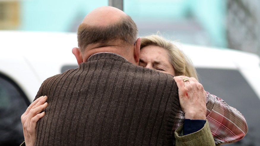 Diane Savage is consoled by Bruce Young in front of St. Paul's By The Sea Episcopal Church, in Ocean City, Md., Tuesday, Nov. 26, 2013. Authorities say two people are dead and another suffered life-threatening injuries after a fire broke out in the rectory of the church. (AP Photo/Salisbury Daily Times, Grant L. Gursky) NO SALES