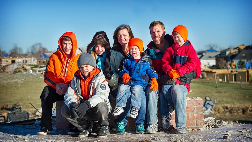 In this November 2013 family photo provided by Annmarie Klein, the Klein family poses in front of the fireplace mantle at their Washington, Ill., home after it was destroyed by a Nov. 17 tornado. From left are Logan Klein, 13; Brady Klein, 11; Morgan Klein, 11; Annmarie Klein, 41; Griffin Klein, 2; Eric Klein, 44; and Owen Klein, 5. Annmarie Klein is asking for the public's help in locating three cards swept away by the twister, each of which Klein's brother, Paul McLaughlin, personalized with a note before his 2005 death from colon cancer. McLaughlin had entrusted Klein to give the cards to his children someday. (AP Photo/Kara Kamienski via Annmarie Klein)