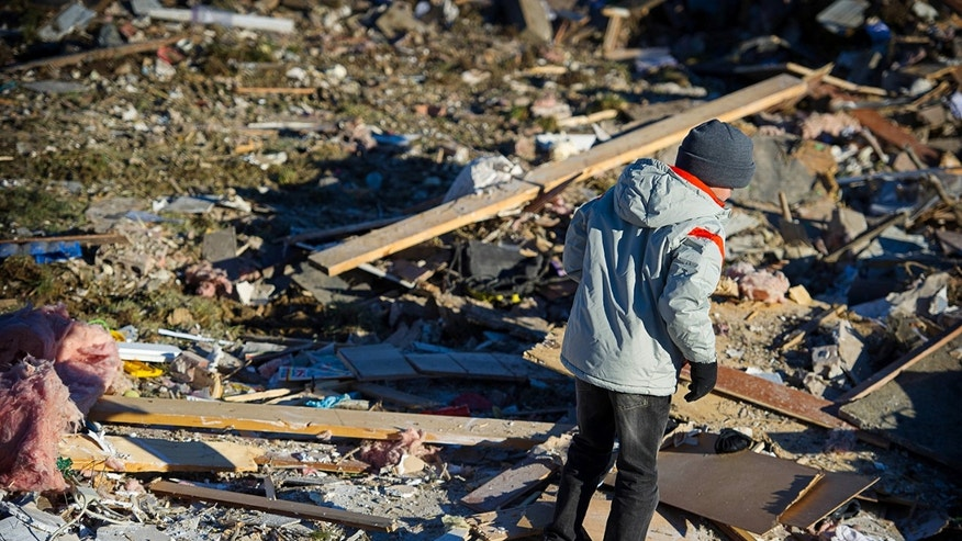 In an November 2013 family photo provided by Annmarie Klein, Brady Klein, 11, walks through the rubble of his family's home in Washington, Ill., after it was leveled Nov. 17 by a tornado. Brady's mother, Annmarie Klein, is asking for the public's help in locating three cards swept away by the twister, each of which Klein's brother, Paul McLaughlin, personalized with a note before his 2005 death from colon cancer. McLaughlin had entrusted Klein to give the cards to his children someday. (AP Photo/Kara Kamienski via Annmarie Klein)