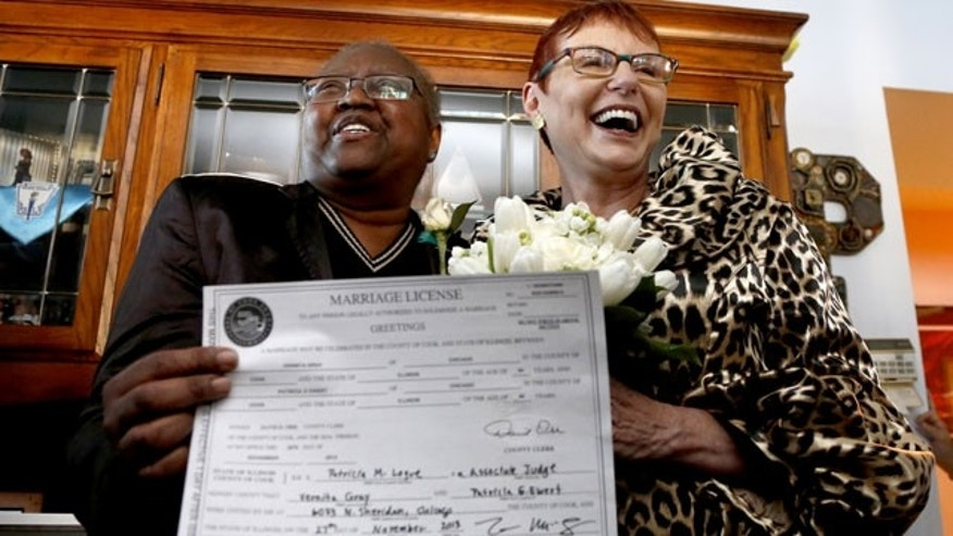 November 27, 2013: Holding their Illinois marriage license, Vernita Gray, left, and Patricia Ewert smile at friends after they were married by Cook County Judge Patricia Logue, at the couple's home in Chicago. U.S. District Judge Thomas Durkin ordered the Cook County clerk Monday to issue an expedited marriage license to Gray and Ewert before the state's gay marriage law takes effect in June 2014, because Gray is terminally ill. (AP Photo/