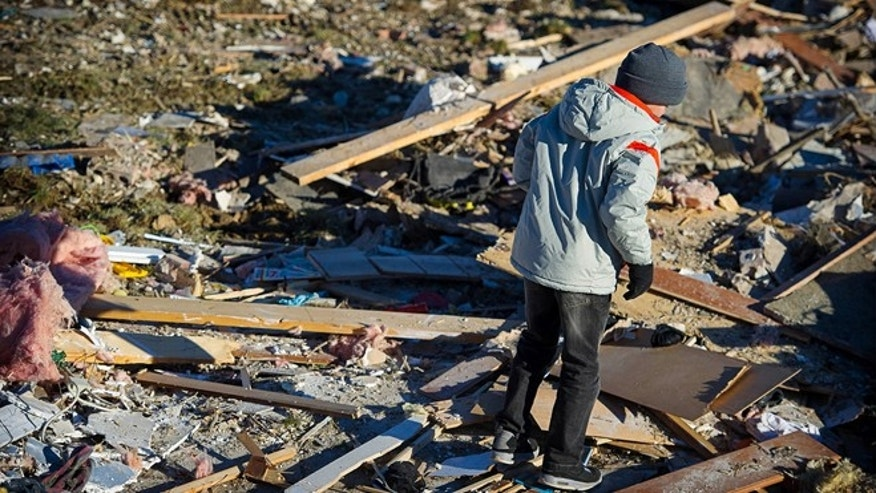 In an November 2013 family photo provided by Annmarie Klein, Brady Klein, 11, walks through the rubble of his familys home in Washington, Ill., after it was leveled Nov. 17 by a tornado. Bradys mother, Annmarie Klein, is asking for the public's help in locating three cards swept away by the twister, each of which Kleins brother, Paul McLaughlin, personalized with a note before his 2005 death from colon cancer. McLaughlin had entrusted Klein to give the cards to his children someday.
