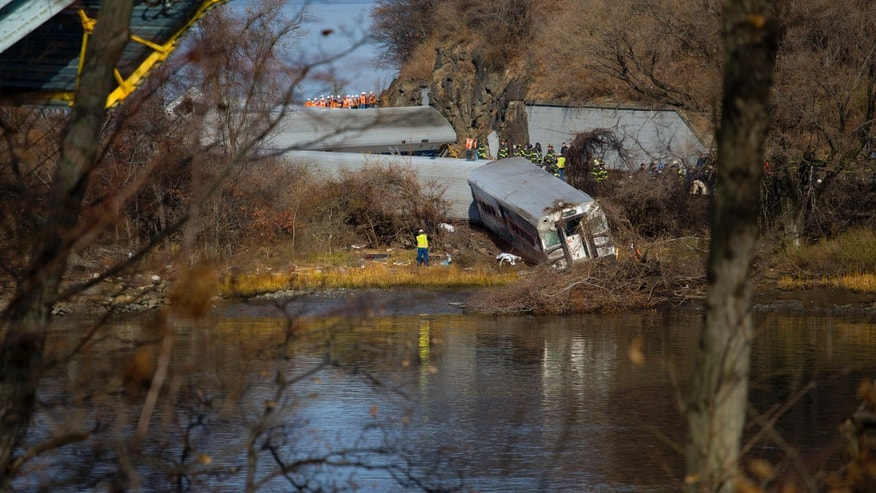 Viewed from Manhattan, Emergency rescue personnel work the scene of a Metro-North passenger train derailment in the Bronx borough of New York, Sunday, Dec. 1, 2013. The train derailed on a curved section of track on Sunday morning, coming to rest just inches from the water and causing multiple fatalities and dozens of injuries, authorities said. Metropolitan Transportation Authority police say the train derailed near the Spuyten Duyvil station. (AP Photo/Craig Ruttle)