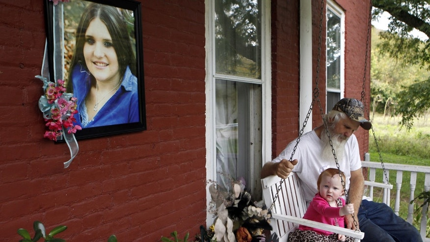 In this October 3, 2013 photo, David Dodson sits with his granddaughter, Aubree Stykes, on the porch of his home in Ripley, Ohio next to a memorial to Dodson's daughter Brittany Stykes, who was killed in an unsolved attack in southern Ohio. Aubree, was shot in the head but has recovered. No arrests have been made, no suspects have been identified and no murder weapon has been found.  Mary Dodson says she had hoped her daughter's killing would be solved by the holidays but now she's afraid it never will be.  (AP Photo/Cara Owsley, The Enquirer, File)