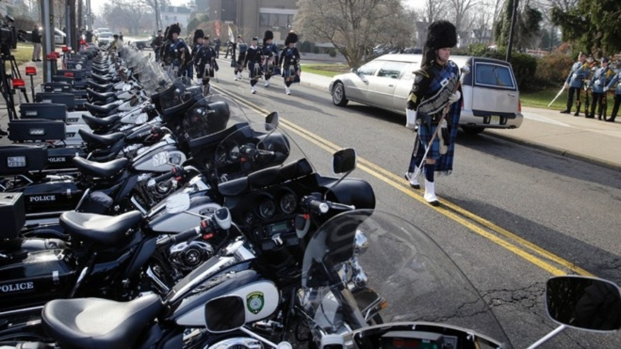 Dec. 3, 2013: A pipe and drum band march past a row of police motorcycles during a procession for Michael Feeney, as Ridgewood, N.J., holds a funeral with full police honors for the 10-year-old boy, Tuesday. Feeney was named Ridgewood's honorary police chief for 2013 before succumbing to cancer last week.
