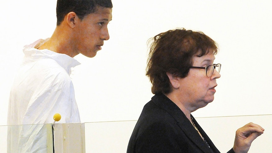 FILE - In this Oct. 23, 2013, file photo, Philip Chism, 14, stands during his arraignment for the death of Danvers High School teacher Colleen Ritzer, as his attorney Denise Regan speaks on his behalf in Salem District Court in Salem, Mass. The 14-year-old Massachusetts boy is set to be arraigned Wednesday Dec. 4, 2013 on murder, aggravated rape and armed robbery charges in the killing of his high school math teacher.  (AP Photo/Boston Herald, Patrick Whittemore, File)
