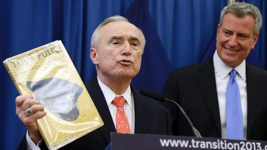 Dec. 5, 2013: William Bratton, left, displays a book he claims influenced his policing from a young age as New York Mayor-elect Bill de Blasio looks on during a news conference in New York. Bratton, whose tenure as New York City police commissioner in the 1990s was marked by a steep decline in crime and clashes with then-Mayor Rudolph Giuliani, has been chosen to lead the nation's largest police force again. De Blasio announced the appointment Thursday, saying Bratton is a 'proven crime-fighter' who knows how to keep the city safe. (AP/Seth Wenig)