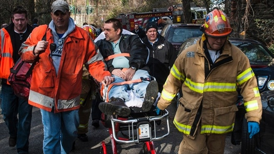 Dec. 1, 2013: Metro North Railroad engineer William Rockefeller is wheeled on a stretcher away from the area where the commuter train he was operating derailed in the Bronx borough of New York.