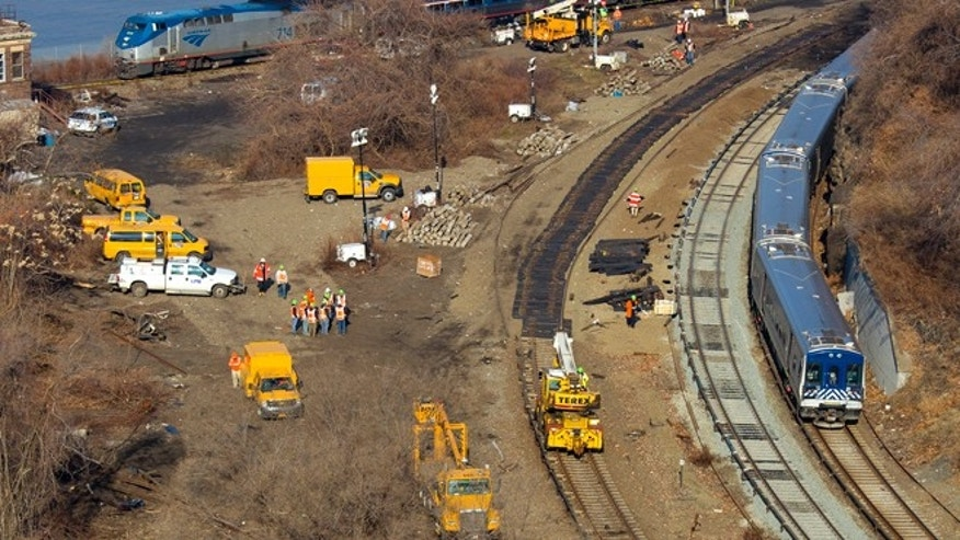 Dec. 4, 2013: A Metro-North Railroad passenger train, right, rounds a sharp curve after pulling out of the Spuyten Duyvil station in the Bronx borough of New York, as crews rebuild the damaged track where a fatal derailment disrupted service on the Hudson Line on Sunday, Dec. 1. An Amtrak train, top, passes by.