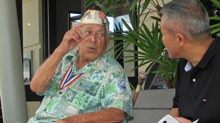 In this photo taken Nov. 22, 2013, Herb Weatherwax, left, talks to a visitor in Pearl Harbor, Hawaii. The 96-year-old retired electrician is one of four Pearl Harbor survivors who volunteers to greet people at the historic site. On Saturday is the 72nd anniversary of the 1941 attack by Japan on Pearl Harbor. (AP Photo/Audrey McAvoy)