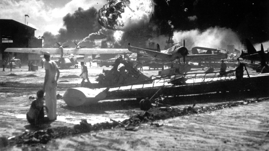 FILE - In this Dec. 7, 1941 file photo provided by the U.S. Navy, sailors stand among wrecked airplanes at Ford Island Naval Air Station as they watch the explosion of the USS Shaw in the background, during the Japanese surprise attack on Pearl Harbor, Hawaii. Saturday marks the 72nd anniversary of the attack that brought the United States into World War II. (AP File Photo)
