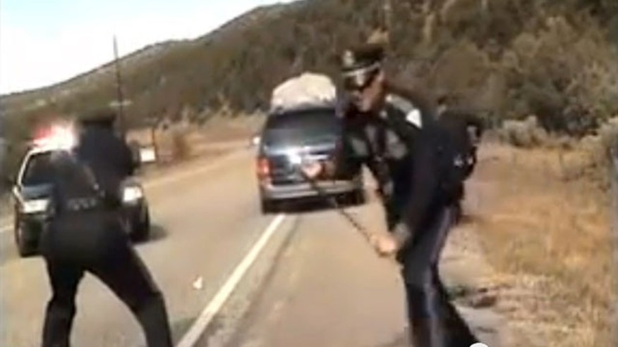 October 28, 2013: Three New Mexico State Police officers react as a minivan driven by motorist Oriana Farrell pulls away from a chaotic traffic stop that included one officer bashing the van'€™s window with his night stick and another, Elias Montoya, at left, firing three shots as the van drives off, in this video made from the dashboard camera of the police cruiser. Montoya, the officer who fired at the van full of children, has been suspended. (AP Photo/New Mexico State Police)