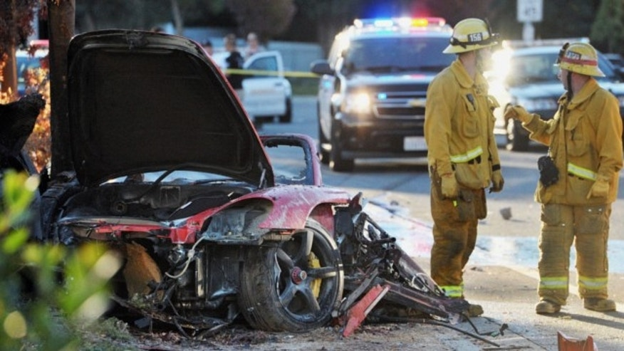"FILE: Nov. 30, 2013: Sheriff's deputies work near the wreckage of a Porsche that crashed into a light pole in Valencia, Calif., killing ""Fast & Furious"" star Paul Walker. Detectives arrested Jameson Witty, 18,  accused of stealing some wreckage from the Porsche."