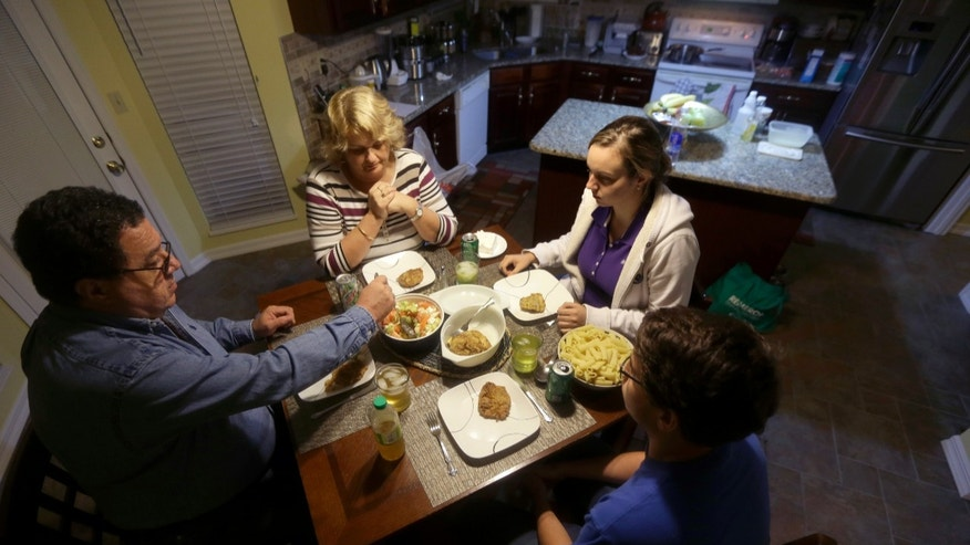 In this photo made Monday, Oct. 21, 2013, Bakir Avdagic, left, sits down to dinner with his wife, Mirha, top, daughter Selma, 22, and son, Amer, 18, bottom right, at their home in O'Fallon, Mo. The Avdagic family are part of an estimated 60,000 Bosnians who live in the St. Louis metropolitan area, making it the largest such settlement outside the country now known as Bosnia-Herzegovina. (AP Photo/Jeff Roberson)