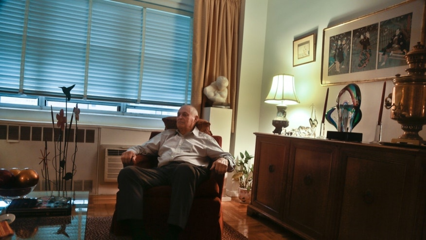 Morton Chalek, 91, a WWII vet and a victim of Bernie Madoff's massive Ponzi scheme, listens during an interview in the apartment he shares with another victim, on Thursday, Dec. 5, 2013 in New York.  With the fifth anniversary of  Madoff's fraud approaching, Chalek is among a legion of former investors still struggling to move on after seeing their life savings go up in flames.  (AP Photo/Bebeto Matthews)