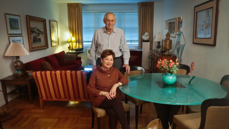 Victims of Bernie Madoff's massive Ponzi scheme, Morton Chalek, 91, standing, a WWII vet, and his friend Fran Reiss, 79, a retired educator,  pose in the apartment they share, on Thursday, Dec. 5, 2013 in New York.  With the fifth anniversary of Madoff's fraud approaching, Chalek and Reiss are among a legion of former investors still struggling to move on after seeing their life savings go up in flames.  (AP Photo/Bebeto Matthews)