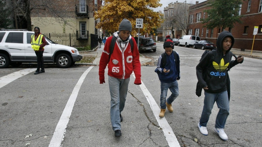 "ADVANCE FOR USE MONDAY, DEC. 9, 2013 AND THEREAFTER - Devion Allen, center in red jacket, an eighth-grader at Chopin Elementary School, walks home on a Safe Passage route with friends in Chicago on Wednesday, Nov. 6, 2013. Allen's former school, Lafayette Elementary, closed in June. He now attends Chopin, which has run into a significant shortage of space since the two schools combined. Officials have dubbed it a ""welcoming school,"" the name given to the Chicago schools that have taken in students from closed buildings. (AP Photo/Martha Irvine)"