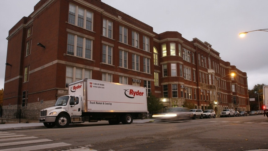 ADVANCE FOR USE MONDAY, DEC. 9, 2013 AND THEREAFTER - A car passes the former Lafayette Elementary School in Chicago on Wednesday, Nov. 6, 2013. Lafayette was one of 47 public schools in Chicago that closed because administrators deemed it underutilized and underperforming. Chicago Public Schools says it will become an arts high school, a contract school that is publicly funded but privately run. (AP Photo/Martha Irvine)