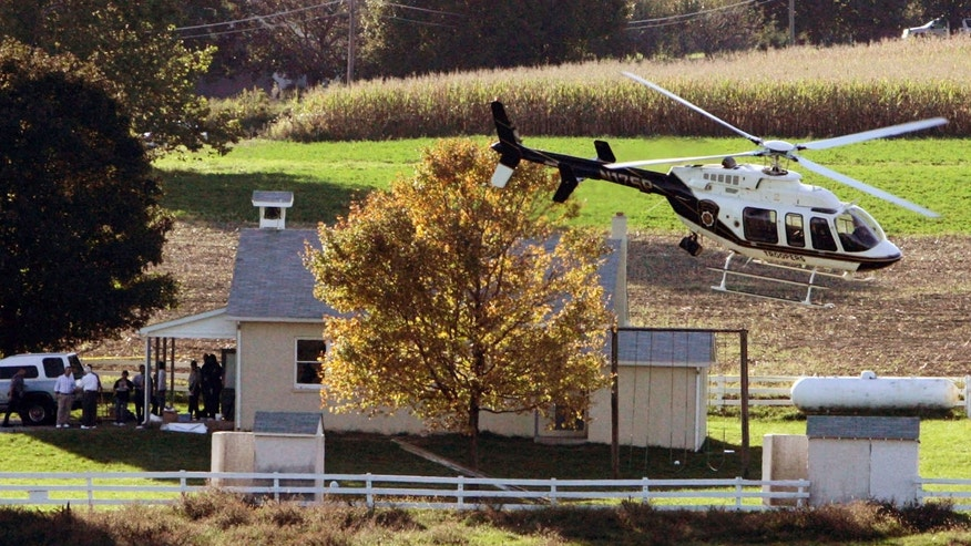 FILE - In this Oct. 2, 2006, file photo, a helicopter takes off from the scene of a mass shooting incident at an Amish schoolhouse in Nickel Mines, Pa. Charles Carl Roberts IV barricaded himself inside the Amish schoolhouse near Lancaster and opened fire, killing five girls and injuring five others before committing suicide as police closed in. (AP Photo/Matt Rourke, File)