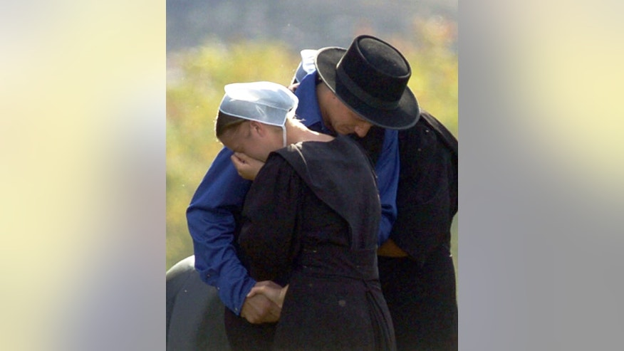 FILE - In this Oct. 3, 2006, file photo, members of the Amish community embracer in Nickel Mines, Pa., near the scene of a mass shooting incident at an Amish schoolhouse. Charles Carl Roberts IV barricaded himself inside the Amish schoolhouse near Lancaster and opened fire, killing five girls and injuring five others before committing suicide as police closed in.  (AP Photo/Pittsburgh Post-Gazette, Andy Starnes, File) ** MAGS OUT  NO SALES **